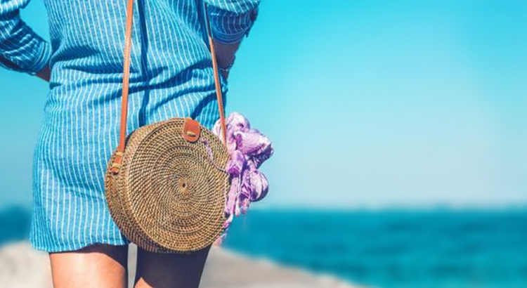 Mulher caminhando na praia com bolsa de palha redonda