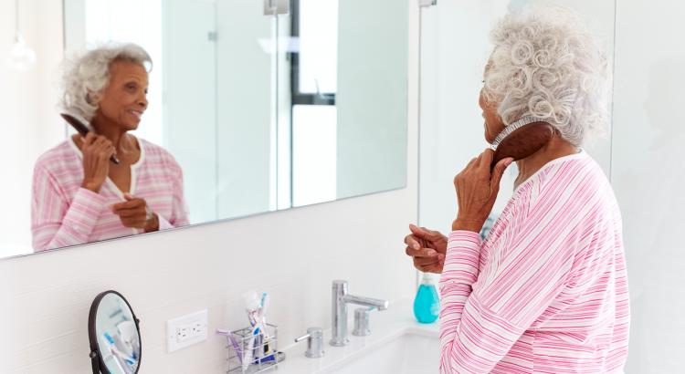 Mulher madura em frente ao espelho penteando o cabelo