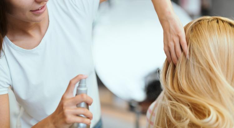 Mulher perfumando o cabelo com spray no salão