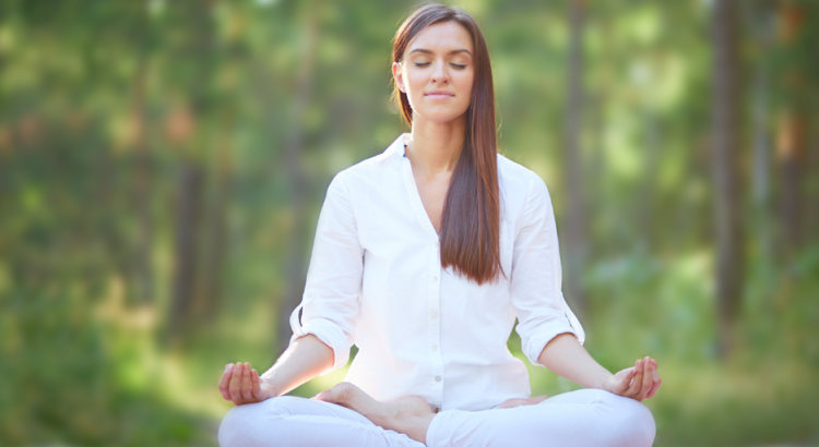 Mulher sentada na grama meditando