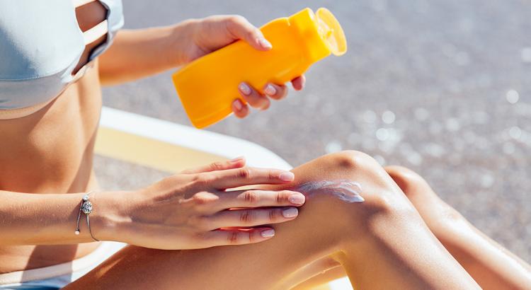 Mulher passando protetor solar para proteger a pele do sol